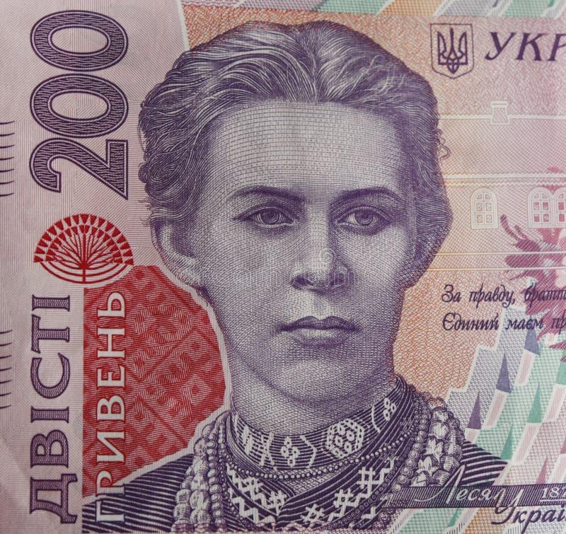 Ukrainska pengar Sedel av den ukrainska hryvniaen Bakgrund av tvåhundra hryvniasedlar, mynt i högar, närbild arkivbilder