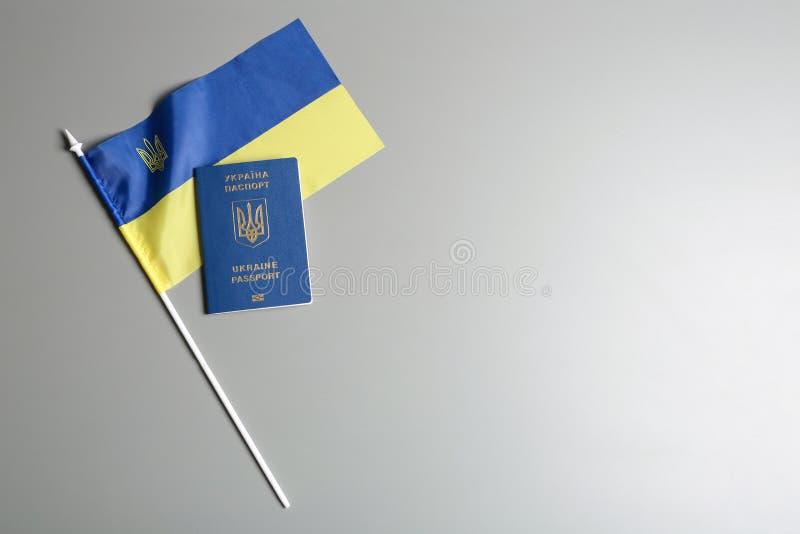 Ukrainskt lopppass och nationsflagga på grå bakgrund, bästa sikt med utrymme för text internationellt arkivfoto