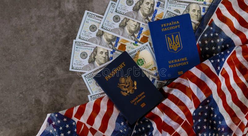 Ukrainskt pass och amerikanskt pass i USA-flaggan med räkningar av hundra dollar arkivbilder