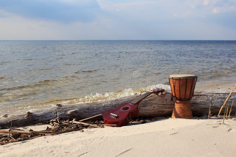 Ukulélé et tambour ethnique sur une plage ensoleillée photos stock