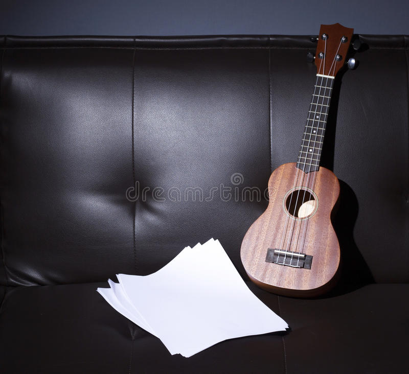 Ukulele and Blank Music Paper. Ukulele and Blank Music Paper Notes on Brown Leather Sofa stock photo