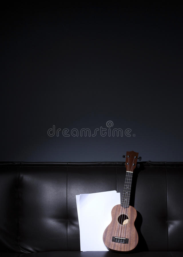 Ukulele and Blank Music Paper. Ukulele and Blank Music Paper Notes on Brown Leather Sofa stock photos