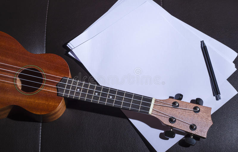 Ukulele and Blank Music Paper. Notes on Brown Leather Sofa royalty free stock photography
