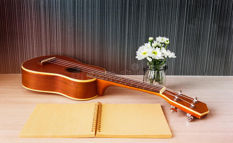 Ukulele and blank note book and flower for love music concept. Ukulele and blank note book with flower for love music concept royalty free stock images