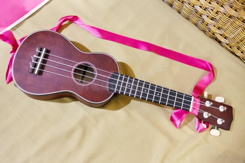 Ukulele con la tracolla rosa del nastro sul backgrou del materasso fotografie stock