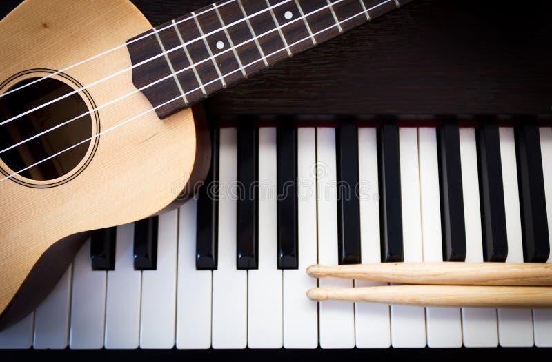 Ukulele with drum sticks on piano. royalty free stock photo