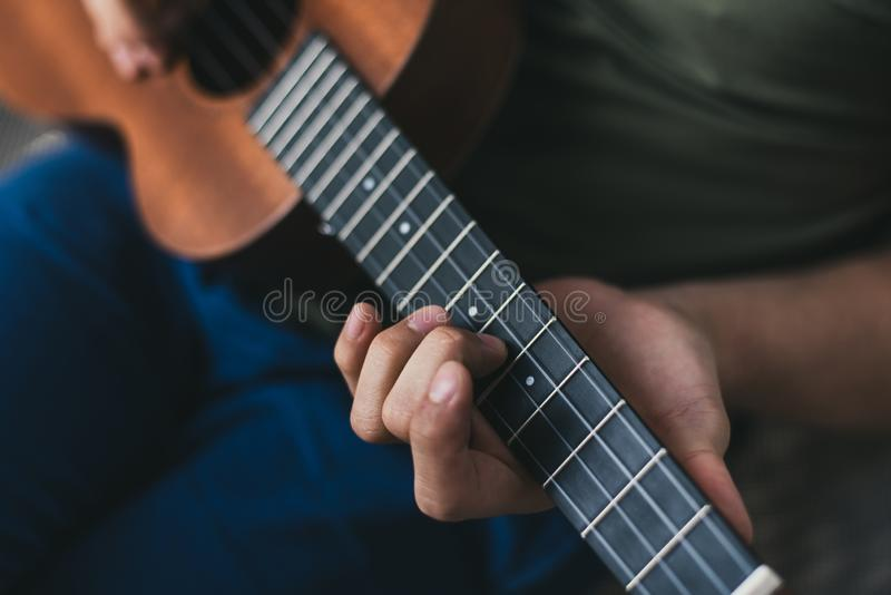 Ukulele game. a man playing a little guitar. the performer writes the music on the ukulele at home.  royalty free stock photography