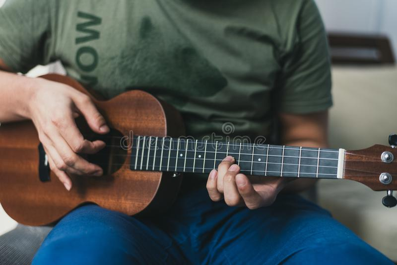 Ukulele game. a man playing a little guitar. the performer writes the music on the ukulele at home.  stock images