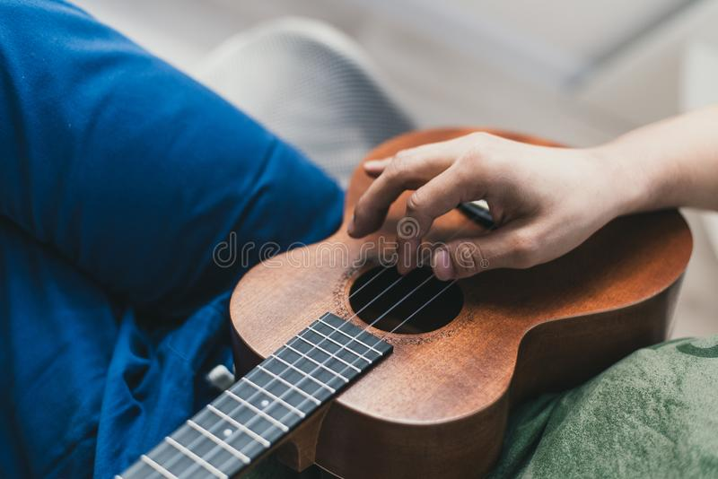 Ukulele game. a man playing a little guitar. the performer writes the music on the ukulele at home.  stock photo