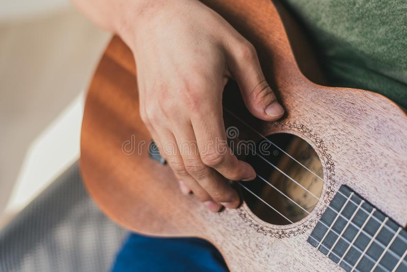 Ukulele game. a man playing a little guitar. the performer writes the music on the ukulele at home. Ukulele game. a man playing a little guitar. the performer royalty free stock photos