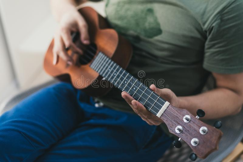 Ukulele game. a man playing a little guitar. the performer writes the music on the ukulele at home. Ukulele game. a man playing a little guitar. the performer stock photos