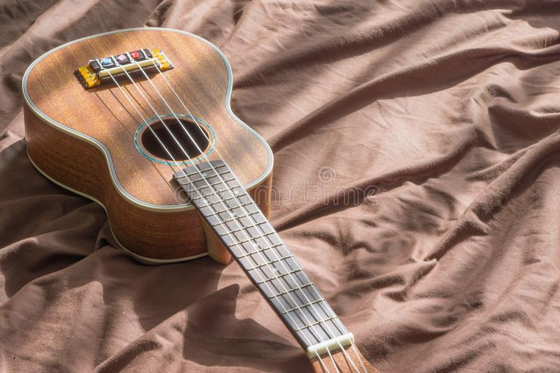 Ukulele guitar on bed background. royalty free stock photo