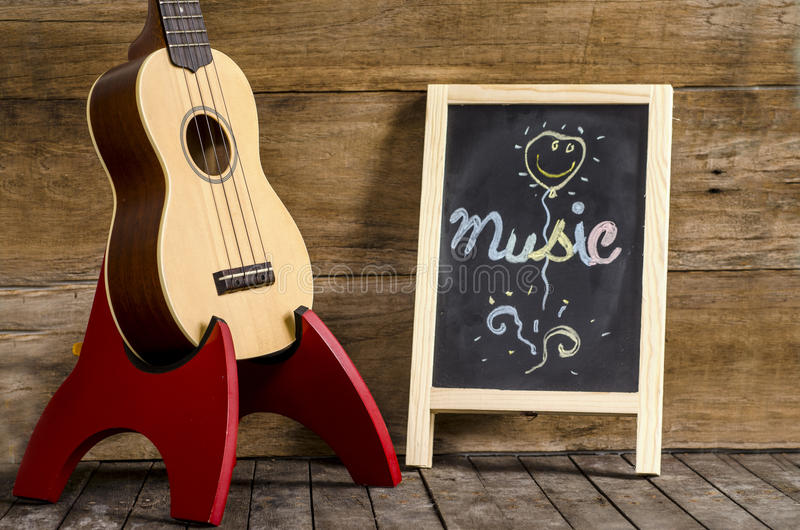 Ukulele guitar and blackboard with the word Music written on wooden background royalty free stock image