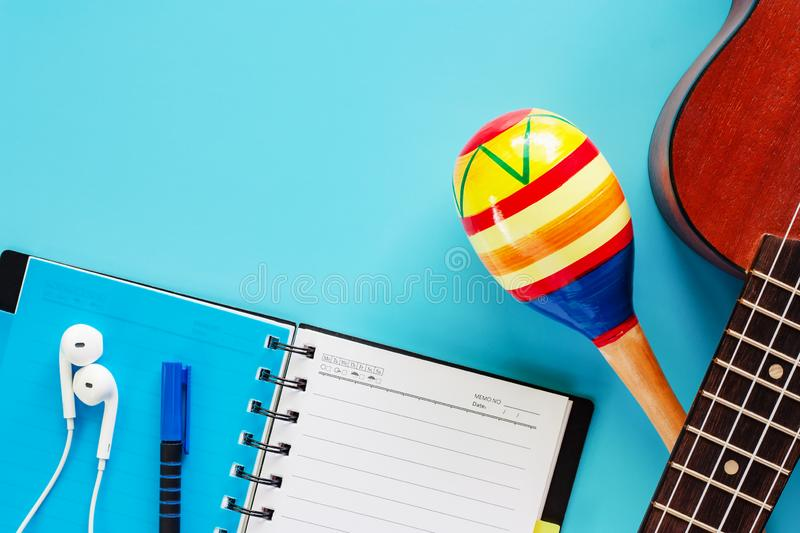Ukulele with maracas, opened spiral notebook, pen and earphones. On blue background or musical instrument, hobbies and relaxation concept stock image