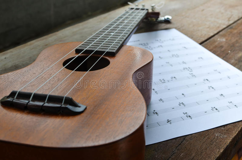 Ukulele with music notepad. A photo of Ukulele with a music notepad in warm light royalty free stock images