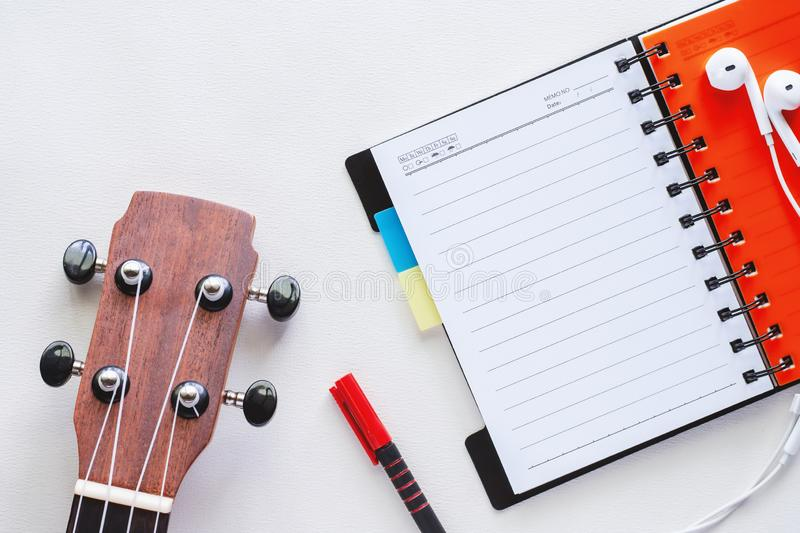 Ukulele with opened spiral notebook, pen and earphones on white. Background for musical instrument and relaxation concept royalty free stock images