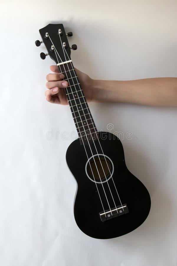 Ukulele, a small black guitar, in the girl`s hand on a white background royalty free stock image