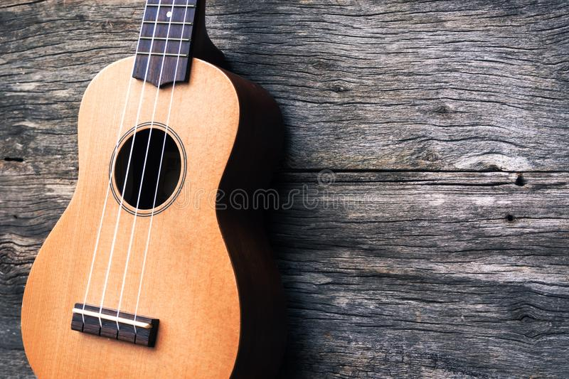 Ukulele with wooden background. Acoustic music instrument. Art a. Nd music background. Vintage style with fade color tone. And dark vignette. Hi contrast style stock image