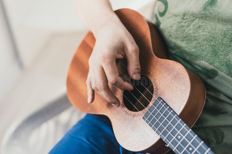 Ukulelelek en man som lite spelar gitarren aktören skriver musiken på ukulelet hemma arkivfoto