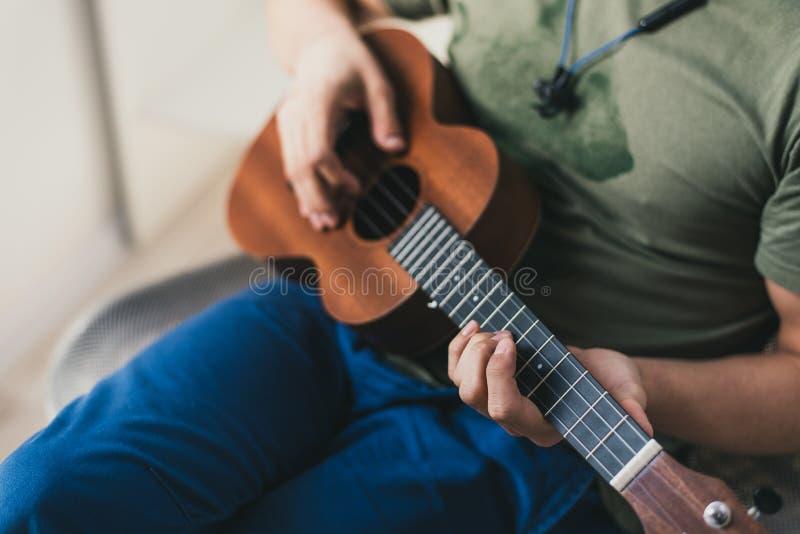 Ukulelespiel ein Mann, der eine kleine Gitarre spielt der Ausführende schreibt die Musik auf die Ukulele zu Hause lizenzfreie stockfotos