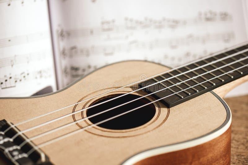 Ukuleli akordy W górę fotografii ukulele muzyki i gitary notatki przeciw drewnianemu tłu instrumenty muzykalni obrazy royalty free