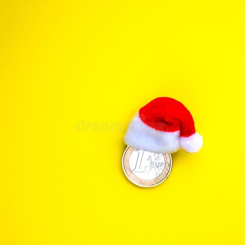 Ukuwa nazwę jeden euro w czerwonym Santa Claus kapeluszu na żółtym tle Pojęcie pieniężni koszty Europejski nowy rok i fotografia royalty free