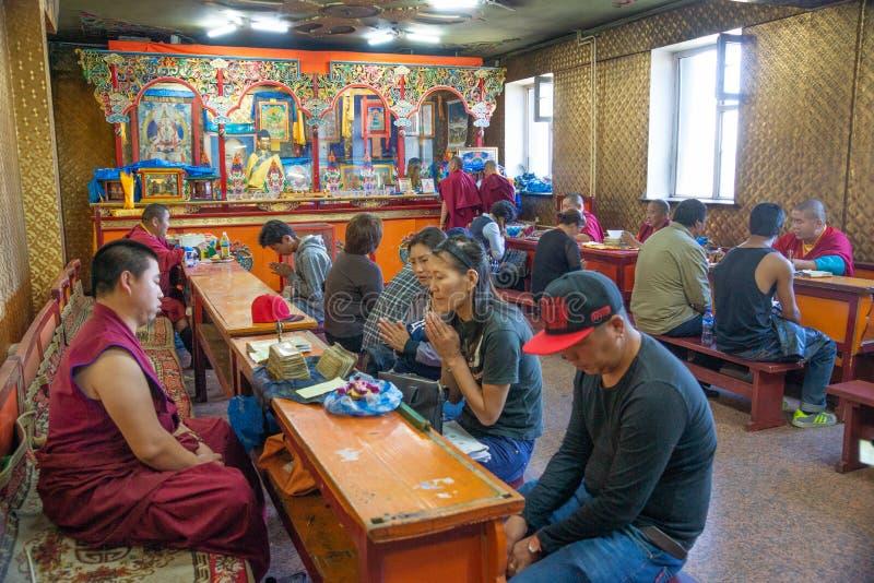 Ulaanbaatar/蒙古12 08 2016年:在寺庙里面的佛教仪式在Ulaanbaatar 祈祷的人们坐和 免版税库存图片