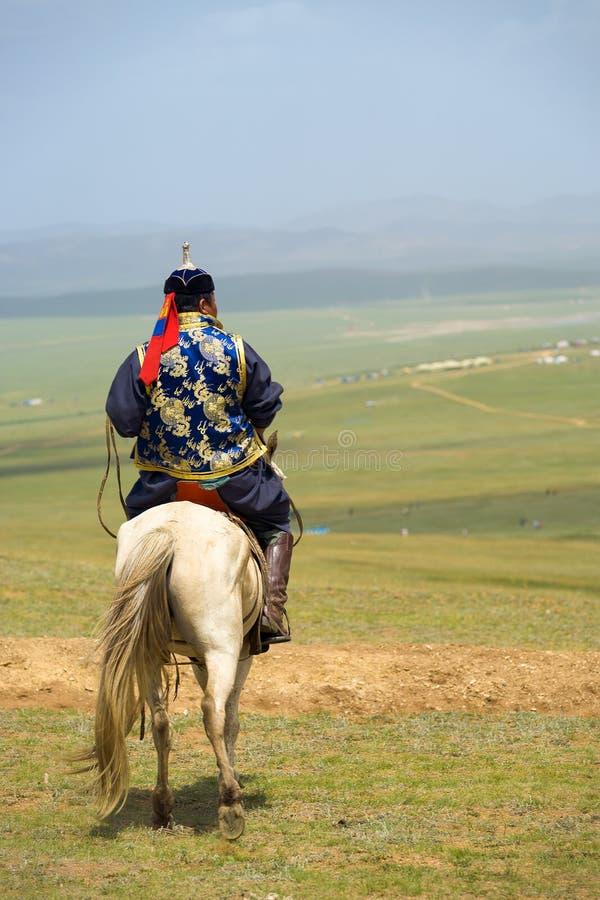 Mongolian Man Horseback Looking Over Steppe stock image