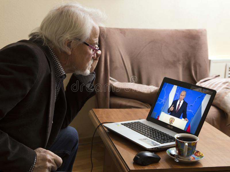 Message to the Parliament of the Russian President. ULAN-UDE, RUSSIA - February 20, 2019: a lonely old man at home watching on TV the annual message of Russian stock photos