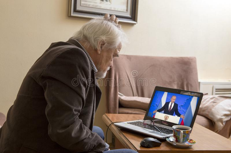 Message to the Parliament of the Russian President. ULAN-UDE, RUSSIA - February 20, 2019: a lonely old man at home watching on TV the annual message of Russian royalty free stock photography