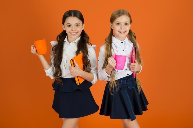 Ulepszać ich nastrój i energię Małe dziewczyny cieszą się szkolne śniadaniowe Śliczne uczennicy trzyma filiżanki i książki trochę zdjęcie stock