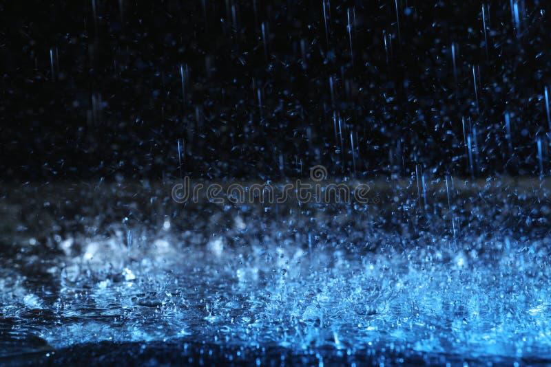 Ulewnego deszczu spada puszek na ziemi przeciw ciemnemu tłu, tonującemu wewnątrz obraz stock