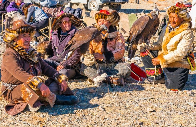 ULGII,蒙古- 2018年10月6日:金鹰节日 哈萨克人在传统衣物的老鹰猎人坐地板等待 库存图片