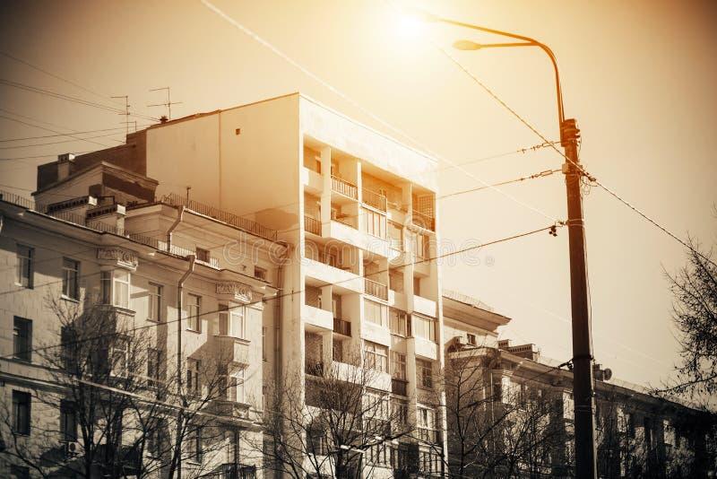 Ulica miejska z drzewami i domami, gdzie latarnia uliczna oświetla ulicę jasnopomarańczowym światłem zdjęcia royalty free