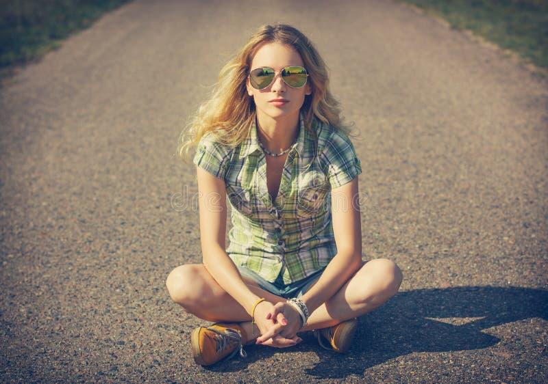 Ulica modnisia dziewczyny Stylowy obsiadanie na drodze obraz royalty free