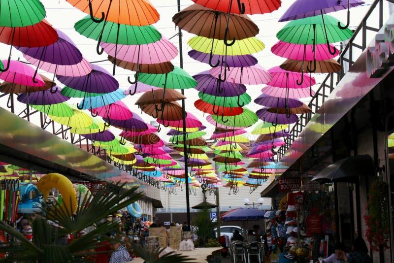 Uliczna instalacja z kolorowymi, pięknymi parasolami unosi się w powietrzu przeciw niebu, obraz stock