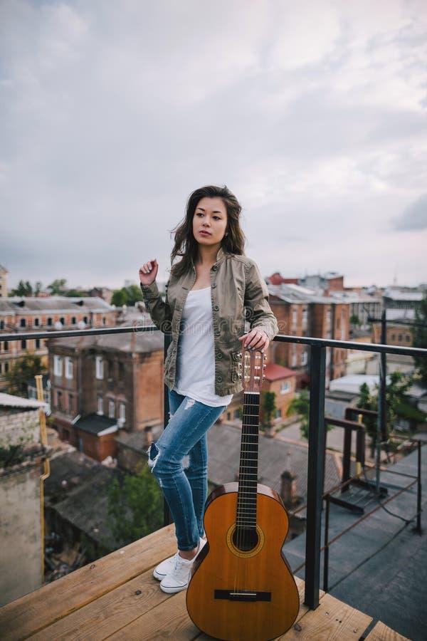 Uliczna muzyka Młoda dziewczyna z gitarą akustyczną zdjęcia royalty free