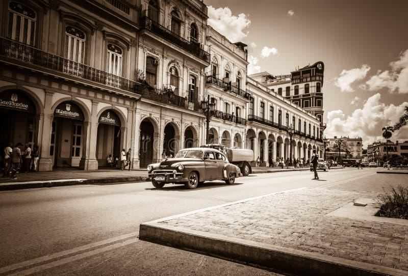Uliczna sceneria na głównej ulicie z prowadnikowymi Amerykańskimi roczników samochodami w Hawańskim Kuba - Retro Seria obraz royalty free