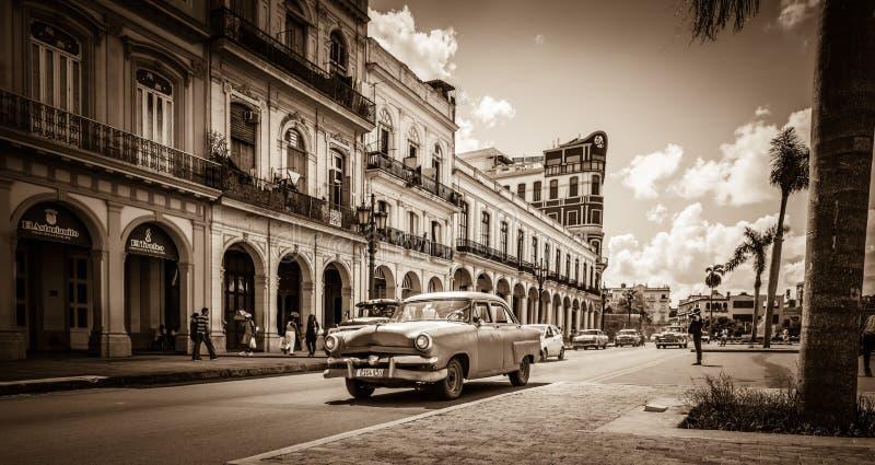 Uliczna sceneria na głównej ulicie z prowadnikowymi Amerykańskimi roczników samochodami w Hawańskim Kuba - Retro Seria Kuba SEPIO zdjęcia stock