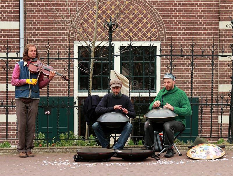 Uliczni muzycy z zrozumienie bębenami i skrzypcowy spełnianie w Amsterdam fotografia royalty free