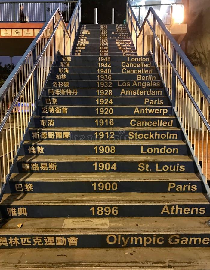 Uliczni wysocy schodki z poręczem nad ziemia w Hong Kong z inskrypcjami o olimpiadach na krokach obrazy stock