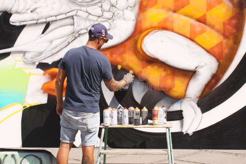 Uliczny artysta maluje kolorowych graffiti na ścianie - sztuki współczesnej pojęcie z miastowym faceta obrazem żyje murales z aer zdjęcia stock