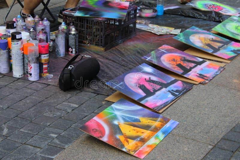 Uliczny artysta maluje puszkę farba na papierze dla nabywc obrazy stock