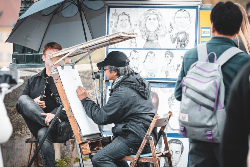Uliczny artysta rysujący portret turystów na moście Charles w Pradze obraz stock