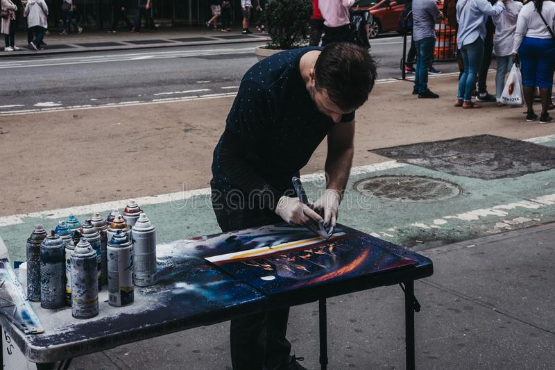 Uliczny artysta tworzy obrazek używać z kiści farbą w czasach obraz royalty free