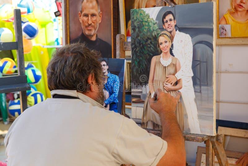 Uliczny malarz robi kopii od fotografii potomstwa dobierać się na kanwie zdjęcie royalty free
