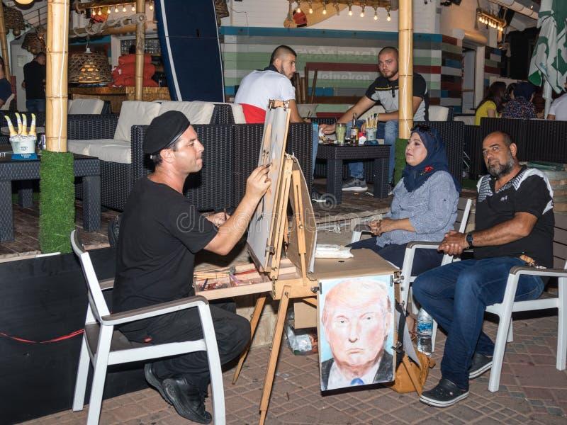 Uliczny malarz siedzi na krześle w wieczór i rysuje ołówek para która pozuje dla on w Nahariya, Izrael zdjęcia royalty free