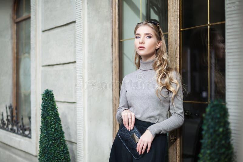 Uliczny mody pojęcie: portret elegancka młoda piękna kobieta pozuje blisko drzwi Talia up tła piękna miasta styl życia miastowi k obraz royalty free