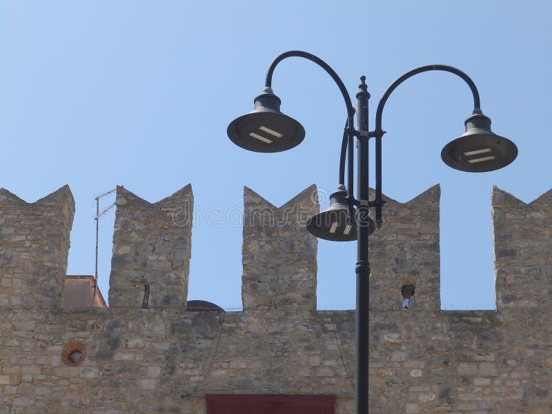 Uliczny oświetlenie przed średniowieczną starą miasta ` s defensywy ścianą fotografia stock