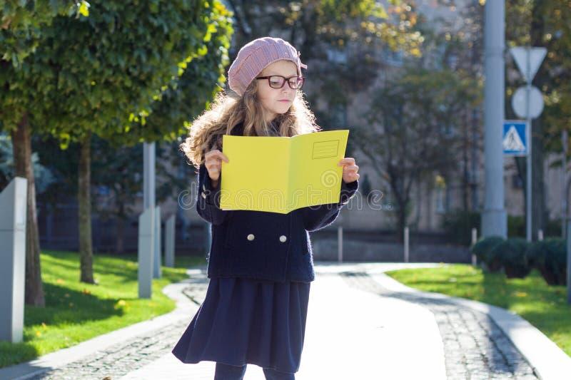 Uliczny portret śliczna dziewczyna w szkłach, żakiet, francuski beret z notatnikiem w rękach obraz royalty free